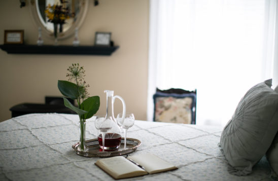 closeup of bed with flower, wine, and book